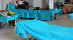 Patients lie in bed at a temporary emergency structure set up outside the accident and emergency department, where any new arrivals presenting suspect new coronavirus symptoms will be tested, at the Brescia hospital, Lombardy, on March 13, 2020. (Photo by Miguel MEDINA / AFP)